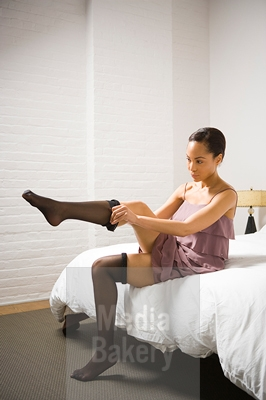 RBI0045747-Woman-putting-on-pantyhose